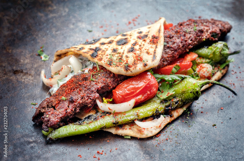 Traditional Adana kebap on a skewer with tomato and yogurt as closeup on a flatbread