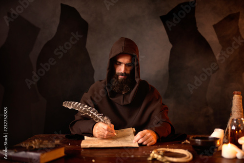 Photo Medieval monk makes notes with a goose feather