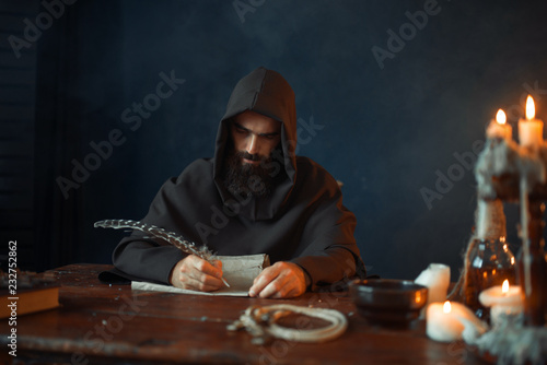 Medieval monk sitting at table and write, top view Fototapeta