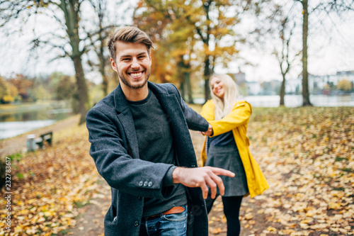 young couple having fun outdoors in autumn park, fall. Loughing and romp around