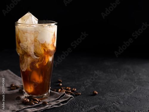 Photographie tall glass cold brew coffee with ice and milk on black or dark background