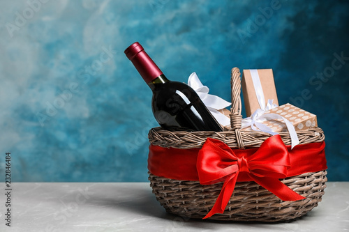 Gift basket with bottle of wine on color background. Space for text
