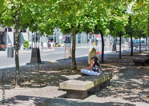 Young woman sitting on bench in city park. Poster Mural XXL