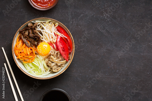 Traditional Asian Bibimbap dish with rice and vegetables on dark background