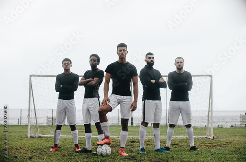 Fotografia Soccer players standing in front of goalpost