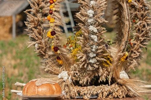 Tradycyjny wieniec dożynkowy z położonym obok chlebem i wplecionymi kwiatami.