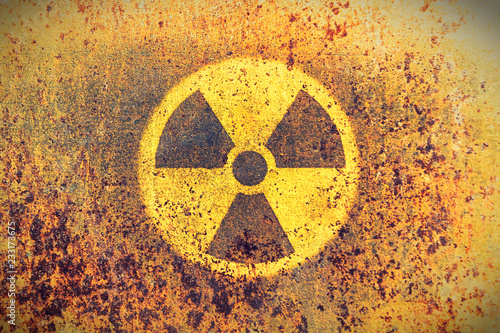 Carta da parati Round yellow radioactive (ionizing radiation) danger symbol painted on a massive rusty metal wall with rustic grunge texture background