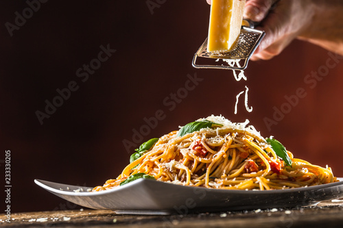 Italian pasta spaghetti with tomato sauce basil and parmesan cheese in white plate