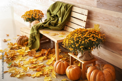 Leinwand Poster Beautiful autumn composition with bench, pumpkins and leaves near wooden wall