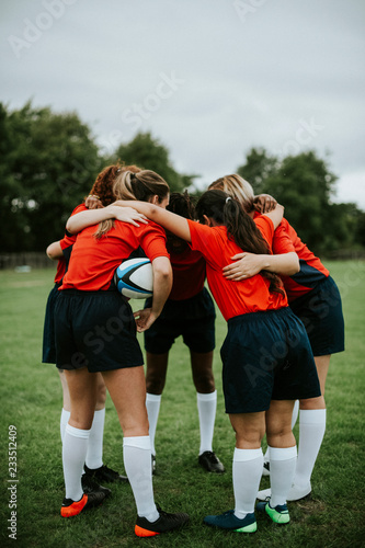 Young female rugby players huddling