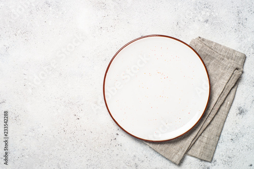 White craft plate and napkin on white stone table.