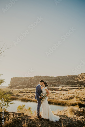 Obraz na plátne Beautiful Couple on their Wedding day in front of landscape