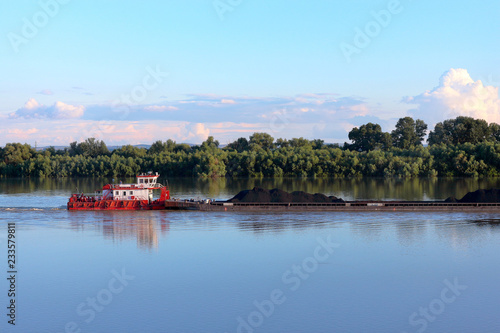 Wallpaper Mural Tugboat pulling heavy loaded barge of black coal along the green trees on the sh