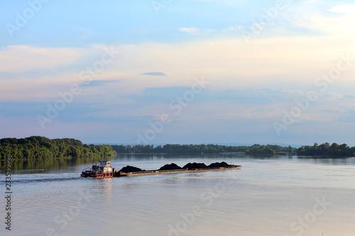 Slika na platnu Tugboat pulling heavy loaded barge of black coal along the green trees on the sh