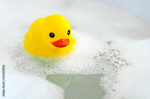 Foto One yellow rubber duck with soap bubble bath, light  background with bubbles
