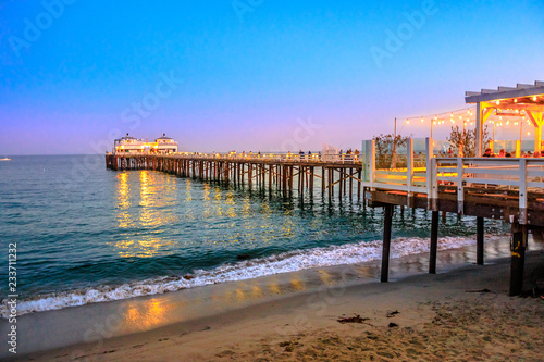Scenic coastal landscape illuminated by night of Malibu Pier in Malibu, California, United States see from Carbon Beach. Malibu Pier is an historic landmark. Blue hour shot. Copy space.