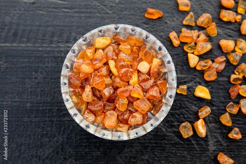 Billede på lærred Flat lay view cute little bowl cup full of small Baltic amber chips on dark brown wooden background