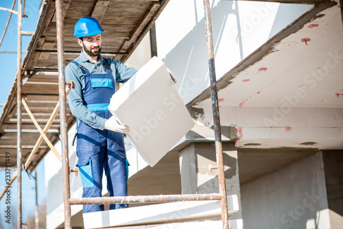 Canvas Print Builder warming a building facade with foam panels standing on the scaffoldings