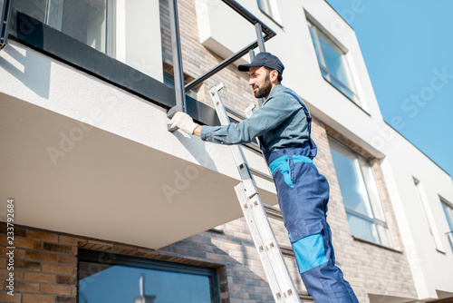 Photo Builder in blue uniform mounting aluminium fence on the balcony of the new build