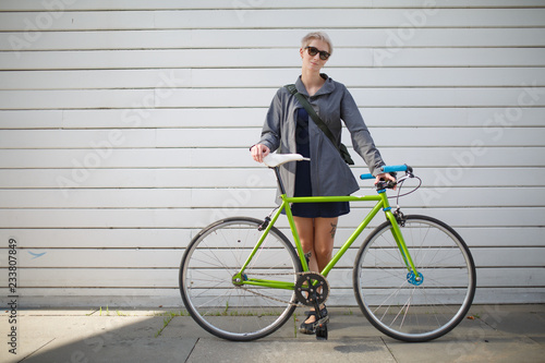 Full-length photo of young woman with green bike near grey wall