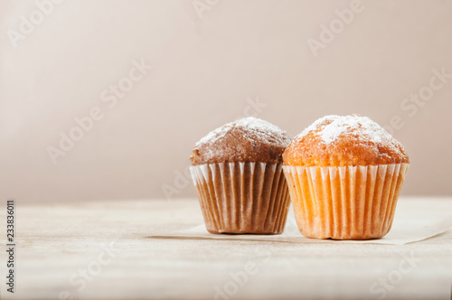 Stampa su Tela Lemon and chocolate muffins on a wooden table. Space for text.