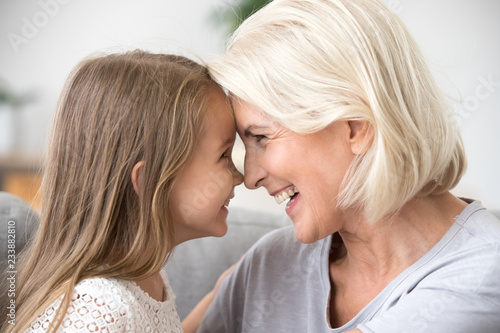 Fototapeta Happy middle-aged mature grandma and little preschool granddaughter touching nos