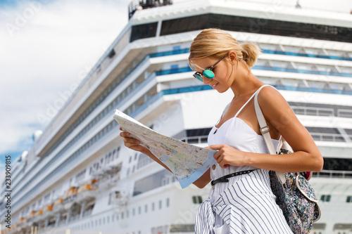 Billede på lærred Woman tourist with map, standing in front of big cruise liner, travel female