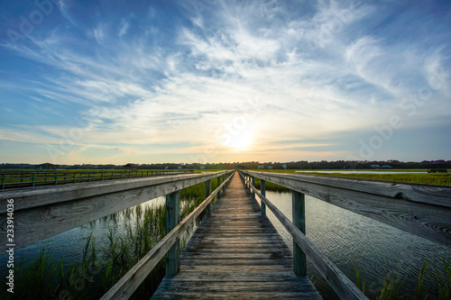 Fotografia coastal waters with a very long wooden boardwalk pier in the center during a col
