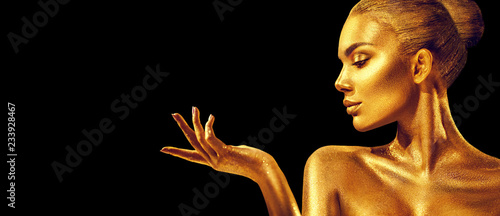 Golden woman. Beauty fashion model girl with golden skin, makeup, hair and jewellery on black background. Fashion art portrait