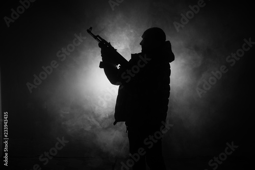 Obraz na plátně Silhouette of man with assault rifle ready to attack on dark toned foggy background or dangerous bandit in black wearing balaclava and holding gun in hand