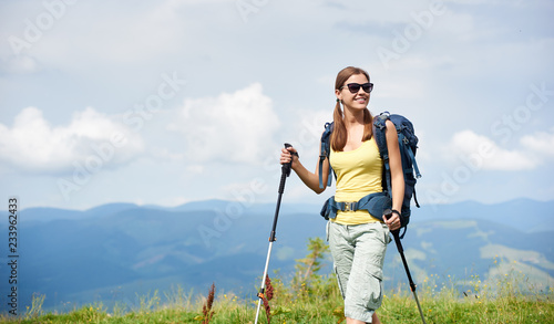 Tablou Canvas Attractive happy woman tourist hiking in Carpathian mountain trail, walking on grassy hill, wearing backpack, sunglasses, using trekking sticks, enjoying summer day