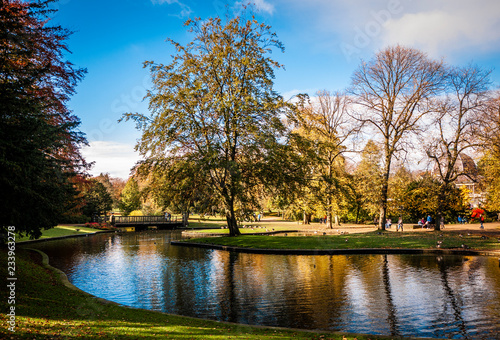 Canvas Print Lovely view of Buxton Park in Autumn, showing the calm pond and beautiful autumnal trees as well as the stone architecture of the town