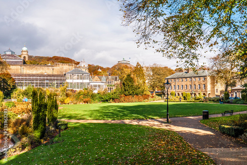 Photo Lovely view of Buxton Park in Autumn, showing the calm pond and beautiful autumnal trees as well as the stone architecture of the town