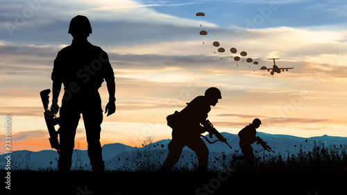 Canvas Print Silhouette of soldiers at sunset watching the launch of paratroopers