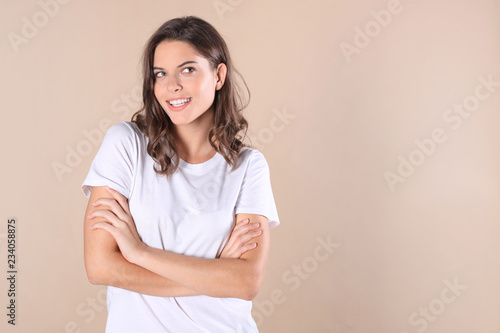 Cuadros en Lienzo Cheerful brunette woman dressed in basic clothing looking at camera, isolated on beige background