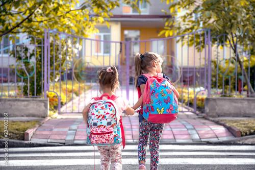 Fotografija Children go to school, happy students with school backpacks and holding hands to