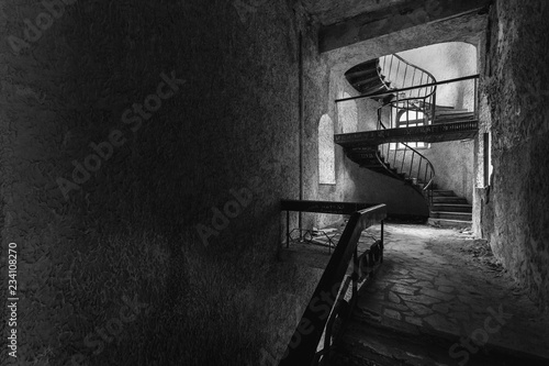 Vászonkép The circular staircase with steps in an abandoned house with copy-space, black and white image