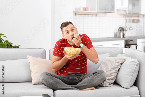 Man with bowl of potato chips sitting on sofa in living room