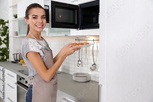 Young woman with plate of croissants near microwave oven in kitchen