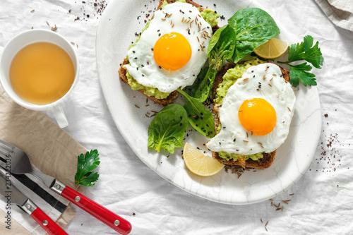 Leinwand Poster Top view healthy avocado toasts breakfast lunch fried eggs cup tea healthy break