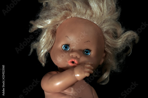 Obraz na plátne Plastic doll on a black background.