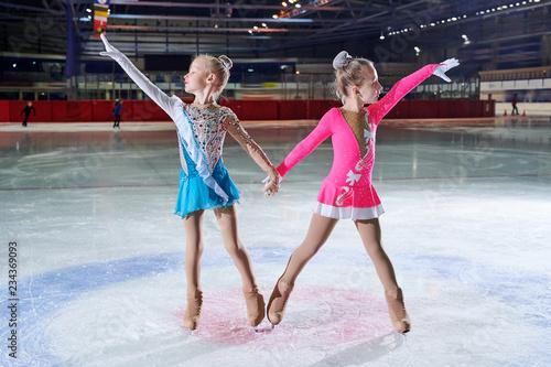 Full length portrait of two little girls posing during figure skating performance in spotlight