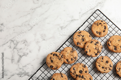 Cooling rack with chocolate chip cookies on marble background, top view. Space for text