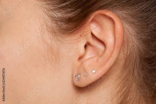 Fotografiet Closeup of female ear with three earrings