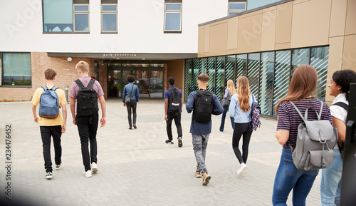 Foto Rear View Of High School Students Walking Into College Building Together