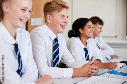 Fototapeta Line Of High School Students Wearing Uniform Sitting At Desk In Classroom