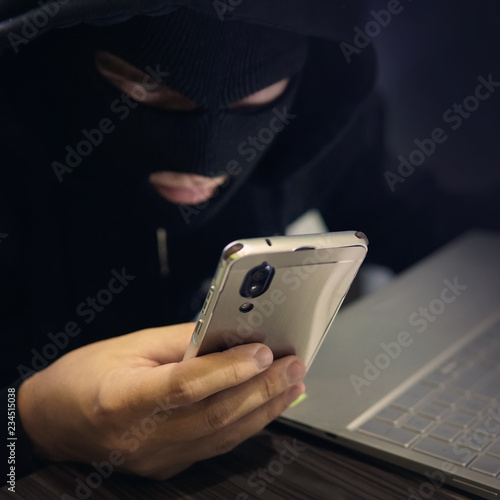 Fotografia Male hacker in a black mask uses smartphone and laptop