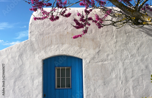 Mediterranean traditional architecture in Ibiza: beatiful small white house with blue door