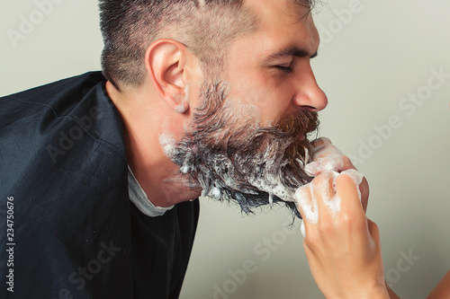 Stampa su Tela Portrait of male client getting his beard washed at salon