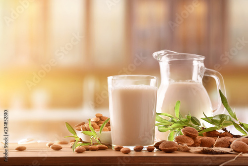 Alternative milk of almonds on wood table in rustic kitchen